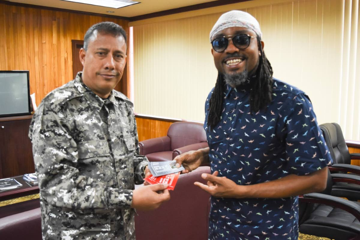 Police Commissioner Gary Griffith, left, receives tickets for Machel Monday from soca star Machel Montano at the Police Administration Building on Sackville Street this afternoon.  PHOTO COURTESY THE TTPS