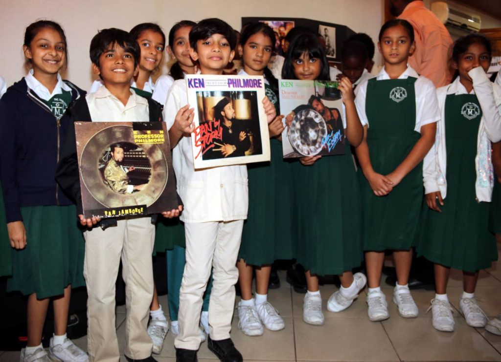 "Students of TML Primary School San Fernando pose with Ken ""Professor"" Philmore records at an exhibition in his honor at City Hall in San Fernando on Tuesday."