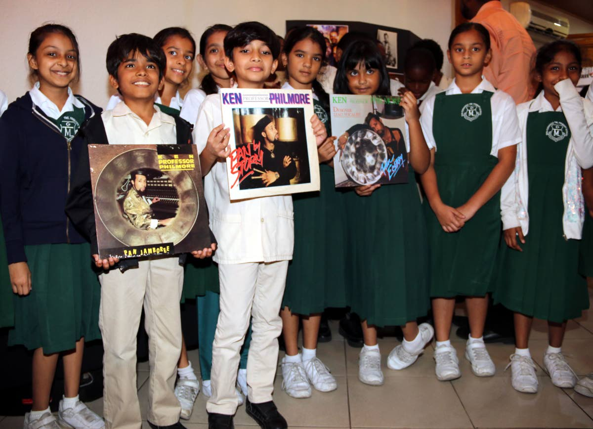 """Students of TML Primary School San Fernando pose with Ken """"Professor"""" Philmore records at an exhibition in his honor at City Hall in San Fernando on Tuesday."""