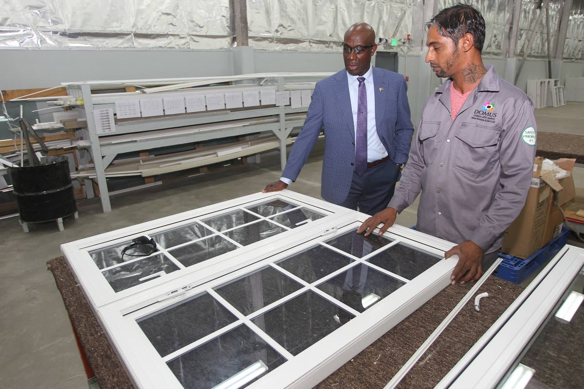 BUSINESS OPENING: Prime Minister Dr Keith Rowley looks at a window yesterday made by Domus Windows and Doors Ltd. PHOTO BY LINCOLN HOLDER