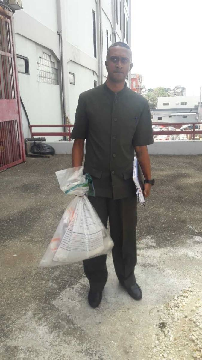 PC Roger Moses carrying a UZI sub-machine gun, three hand guns and 74 rounds of ammunition from San Fernando magistrates' court yesterday