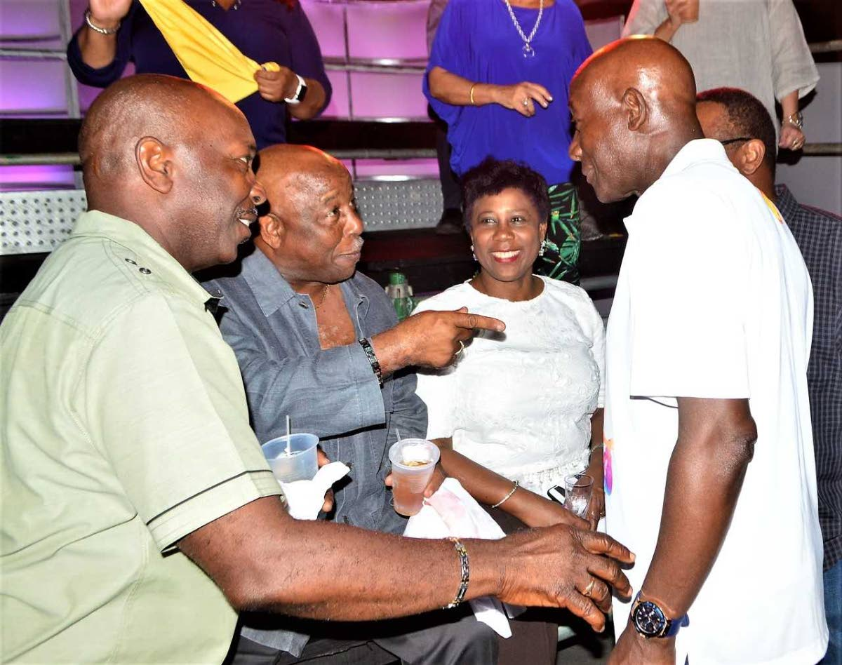 Prime Minister Dr Keith Rowley has the attention of Newman George and Berry Ferdinand, as Speaker Bridgid Annisette-George looks on, at Shell Invaders' Panyard Experience, Queen's Park Oval, Port of Spain on Tuesday evening. Photo by Gary Cardinez