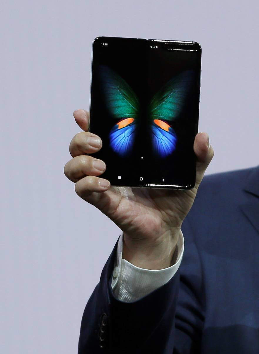 DJ Koh, Samsung president and CEO of IT and Mobile Communications, holds up the new Galaxy Fold smartphone yesterday.