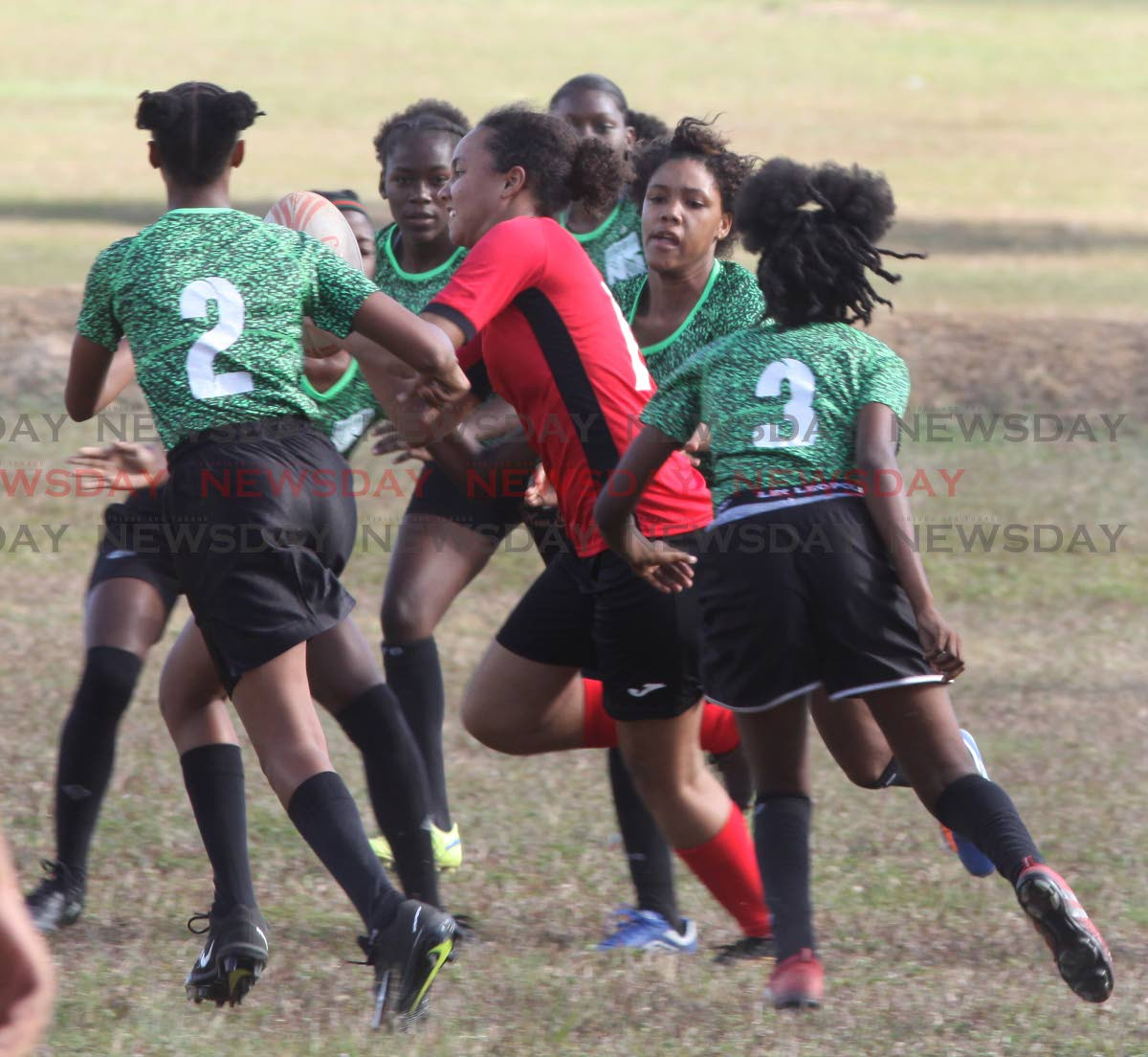 Bishop Anstey's Babi Oura is tackled by six San Juan North players in the Schools Girls Rugby League final yesterday at the Queen's Park Savannah, Port of Spain. PHOTO BY ANGELO MARCELLE