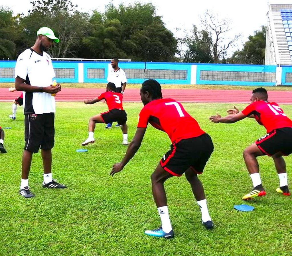 TT men's football coach Dennis Lawrence, left, conducts a training session at the Ato Boldon Stadium in Couva in February. PHOTO BY TTFA MEDIA