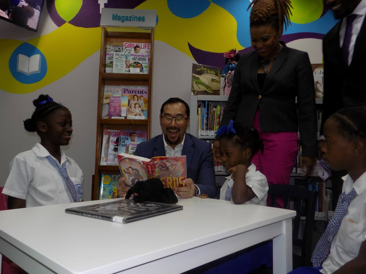 Minister of National Security Stuart Young, second from right, reads to children during the opening of the Beetham Community Library, Beetham Estate, yesterday morning, as Minister of Culture and the Arts Nyan Gadsby-Dolly looks on.