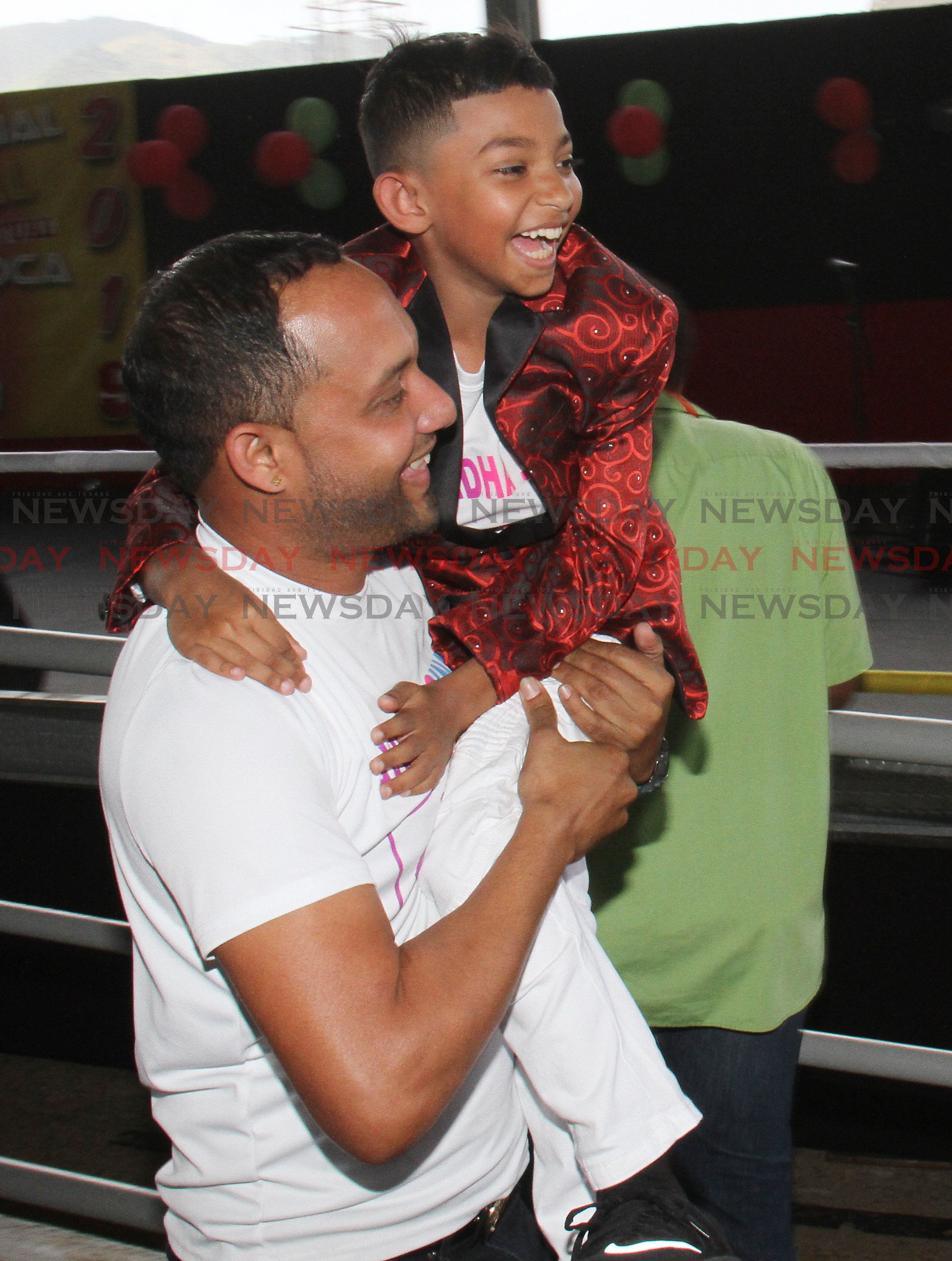 Avindha Singh of Tamana Hindu School, is lifted by his music teacher Rishi Singh, after he won the 2019 School's Intellectual National ChutneySoca Monarch Competition, with his song Take Your Education, in the Primary School category, Grand Stand, Queen's Park Savannah, Port of Spain.  PHOTO:ANGELO M. MARCELLE 27-02-2019