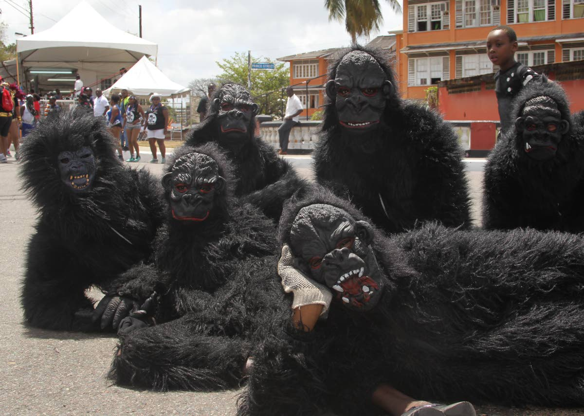 A boy looks curiously at a band of gorillas lying around on Piccadilly Street, Port of Spain on Carnival Tuesday. Piccadilly Street, central to the city's cultural history, and environs will undergo an upgrade. PHOTO BY ROGER JACOB