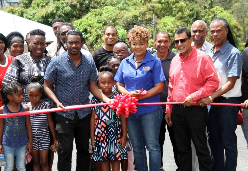 Minister of Community Development, Culture and the Arts Dr Nyan Gadsby-Dolly cuts the ribbon to open a new road in her St Ann's East constituency with Works and Transport Minister Rohan Sinanan, right, residents and officials yesterday. PHOTO BY SUREASH CHOLAI