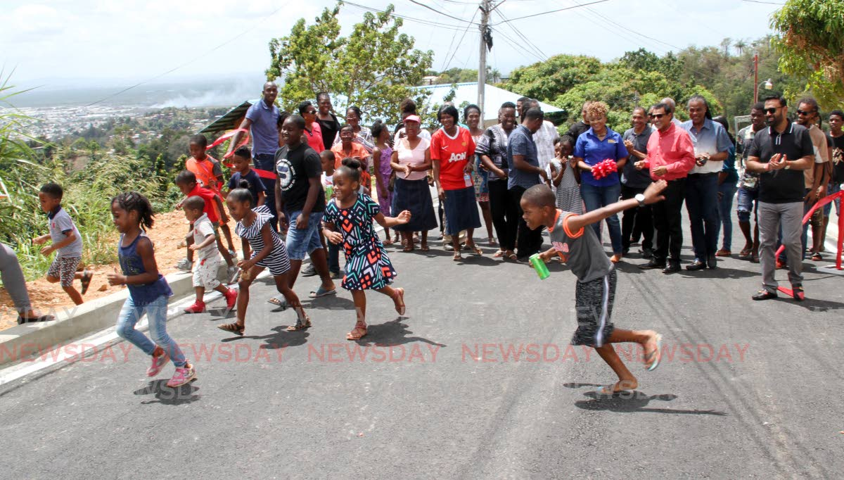 Children happily run across Laventille Road as St Ann's East MP Dr Nyan Gadsby-Dolly and Works and Transport Minister Rohan Sinanan, alongside residents and officials, cut the ribbon to open the road in Febeau Village, San Juan on Saturday. PHOTO BY SUREASH CHOLAI