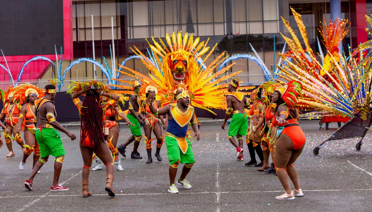 Masqueraders from Astra Winchester's mas band frolic in the street on Carnival Monday in Scarborough. PHOTO BY DAVID REID