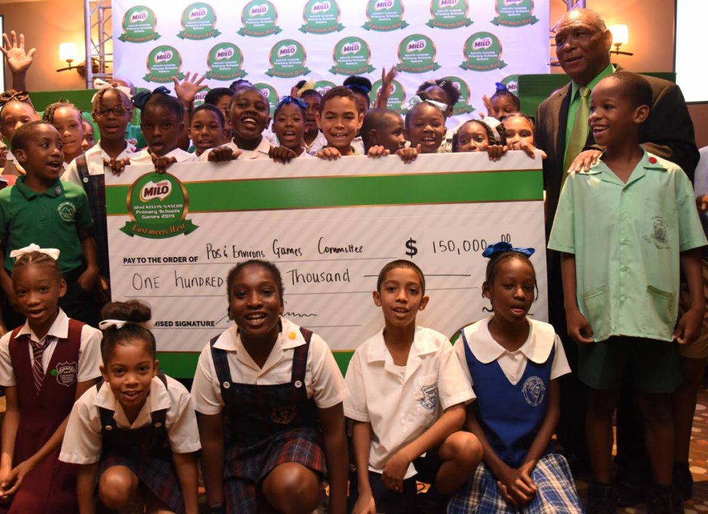 Primary school children display a cheque for $150,000 issued by title sponsor of the 32nd Kelvin Nancoo Games 2019. At right stands chair of the Milo West Games Kelvin Nancoo.