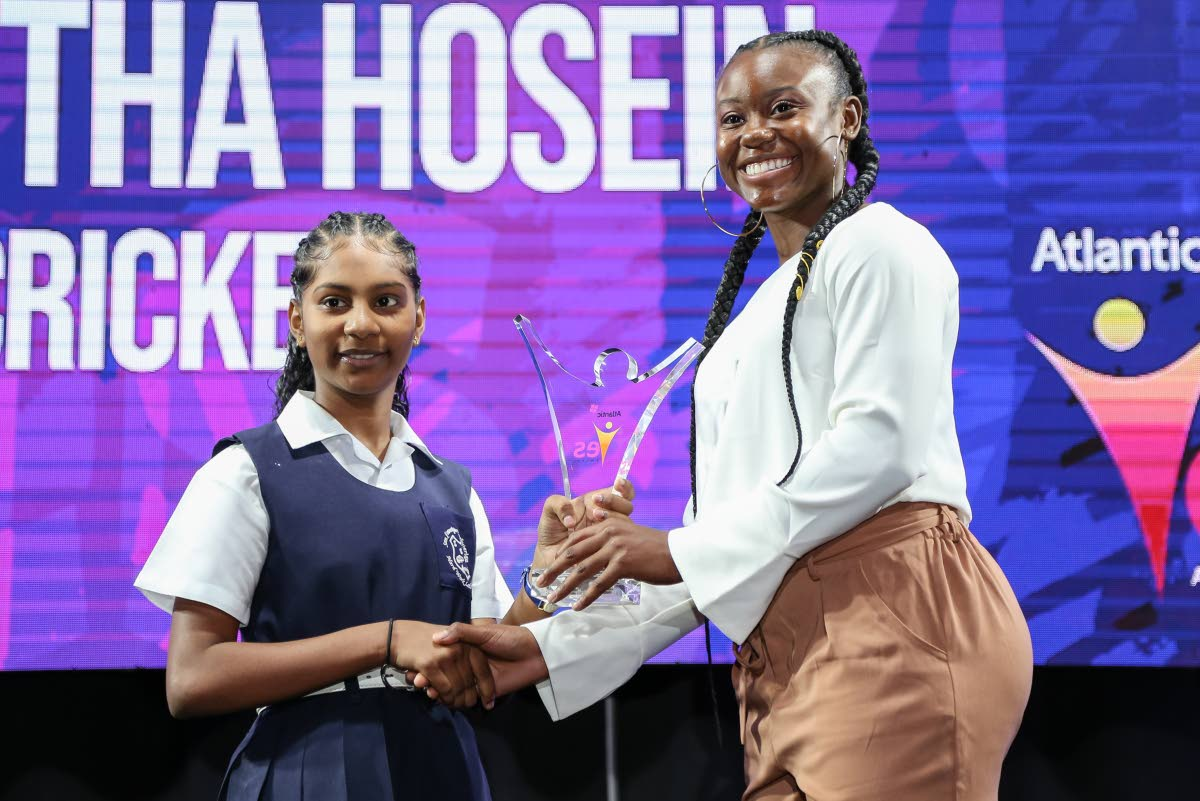 National track star Khalifa St Fort presents the Female Youth Champion of the Year award to Samantha Hosein, of San Francique Presbyterian School during the Atlantanic YES awards,held at the Hilton Trinidad,yesterday.