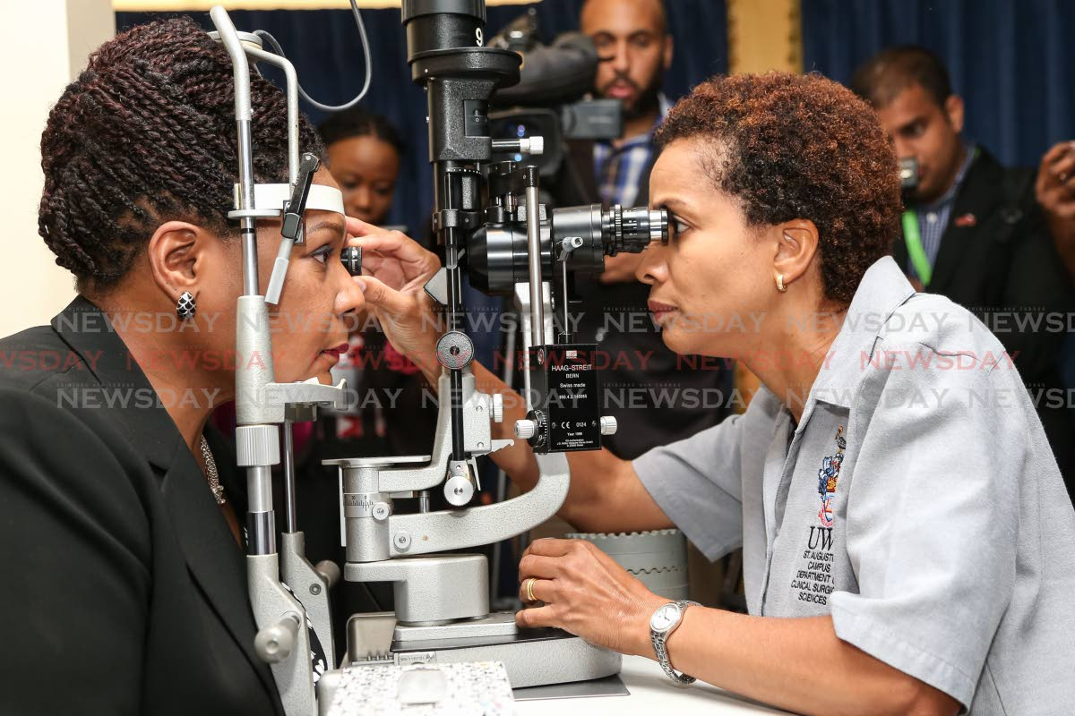 Dr. Desriee Murray conduts Slit Lamp Biomicroscopy on President Paula-Mae Weeks as part of World Glaucoma Week 2019 at the Cottage, Office of the President, St Anns. Photo by Jeff K. Mayers