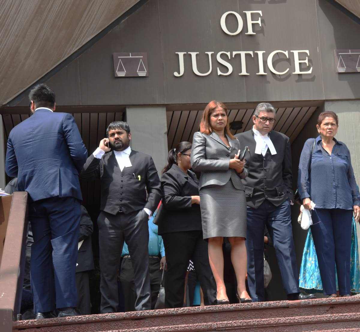 Justice Ricky Rahim, centre, leaves the Hall of Justice, Port of Spain, after fire alarms went off because of a faulty aircondition unit belt.