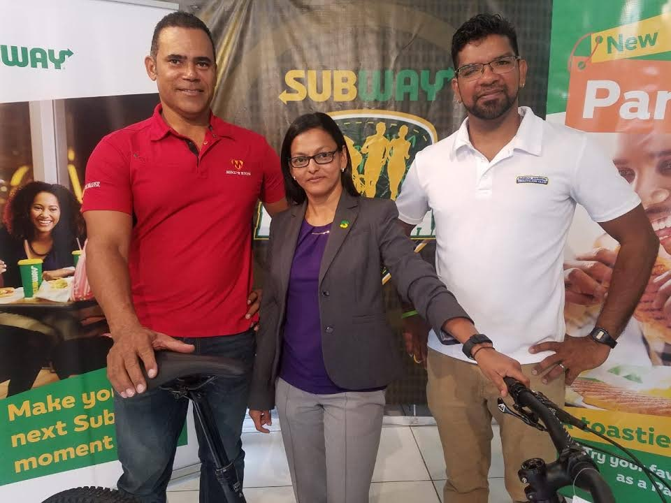 Event manager at Rainbow Warriors Triathlon Club, Jason Gooding, right, with Asha Sanmoogan, Presitige Holdings Marketing Manager, representing Subway, centre, and Michael Phillips, former national cyclist and owner of Mike's Bikes at the launch of the 13th annual Subway River Raid, which was held at Mike's Bikes, Ariapita Avenue, Woodbrook, yesterday.