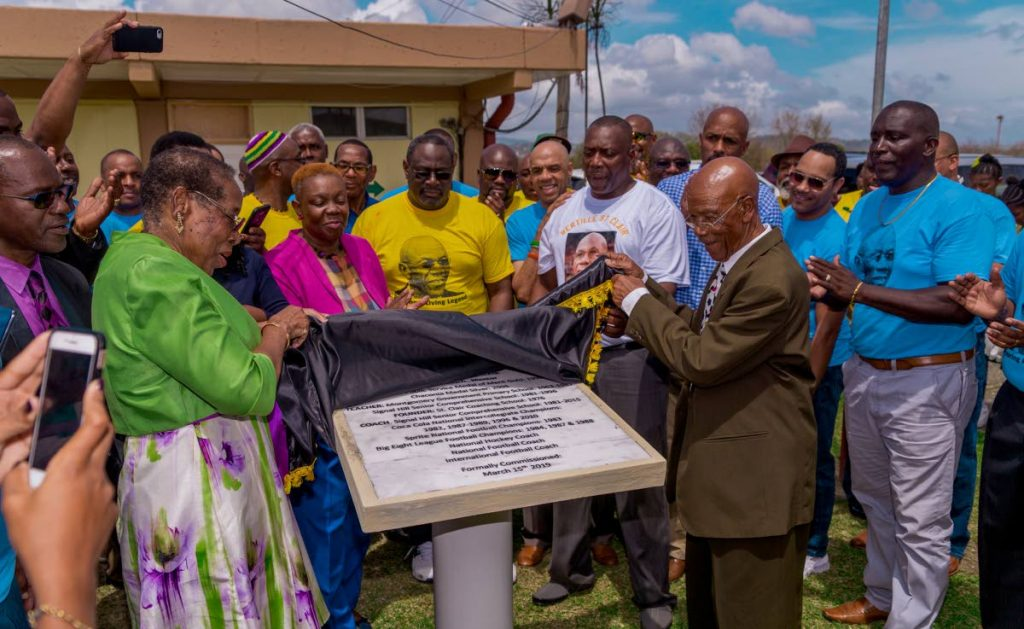 Veteran coach Bertille St Clair, front right, is surprised with a commemorative stone at Signal Hill Secondary yesterday. St Clair is being honoured for three days in Tobago. Looking on are former sports minister Pamela Nicholson, left, and several past footballers.