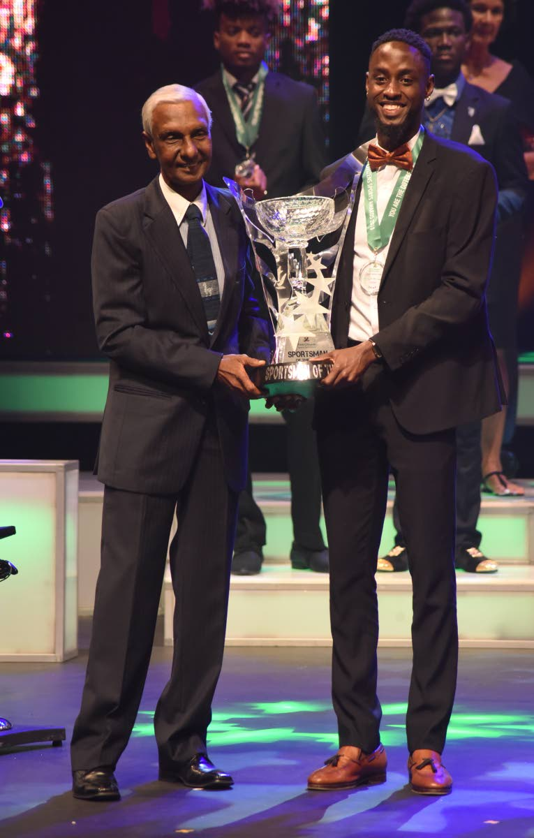 Sportsman of the Year 2018 Jereem Richards, right, collects his award from chairman of the First Citizens Sports Foundation Dr Terry Ali at the awards ceremony on Saturday, held at Queen's Hall, Port of Spain. PHOTO BY KERWIN PIERRE