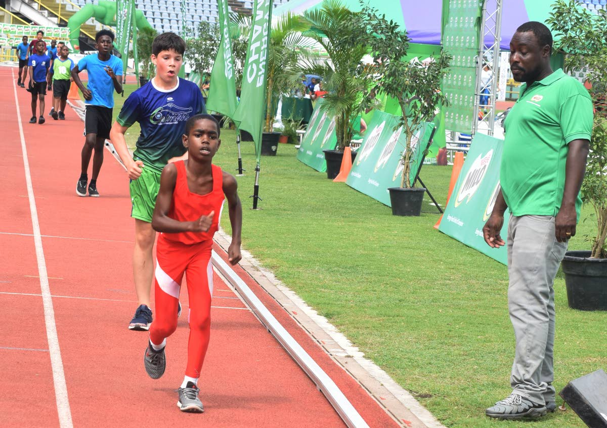 Jareem Mondezie, foreground, from Diamond Vale Govement School, looks to cross the finish line in frist place in the boys open walk 400m at the 32nd Kelvin Nancoo Primary School Milo Games,yesterday.