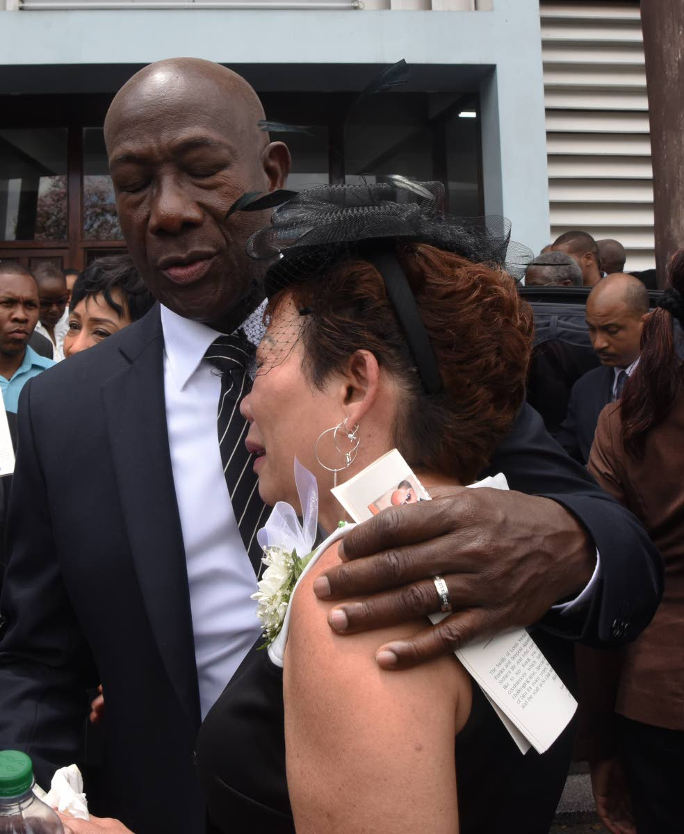 Prime Minister Dr Keith Rowley comforts Sherlyn Monteil during the funeral of her son Stefan---Flavorite Foods Ltd CEO and Yuma bandleader---at Assumption Church, Maraval on Friday. PHOTO BY KERWIN PIERRE
