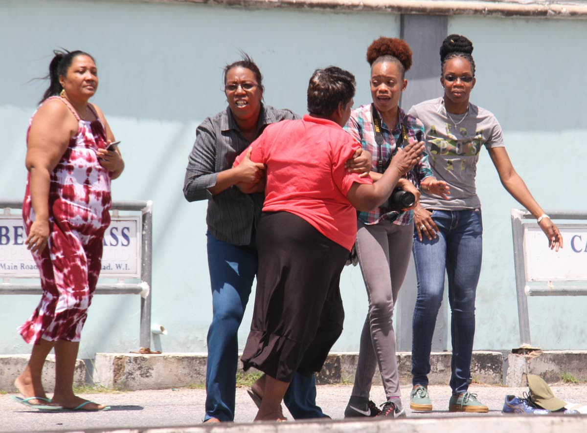 SORROW: Relatives of Michael Barry console each other at the scene yesterday along the Priority Bus Route in Barataria where he was knocked down and killed by a marked police SUV while trying to cross the road. PHOTO BY ANGELO MARCELLE