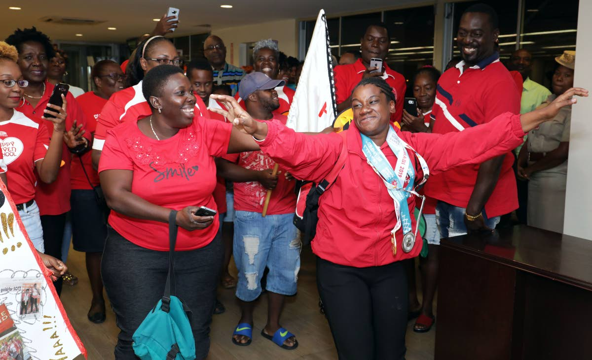 Teachers and pupils of the Happy Haven school celebrate Special Olympian Sapphire Jackson on her arrival, at a welcome reception, in the international departure lounge, of the ANR Robinson International airport, on Friday night.