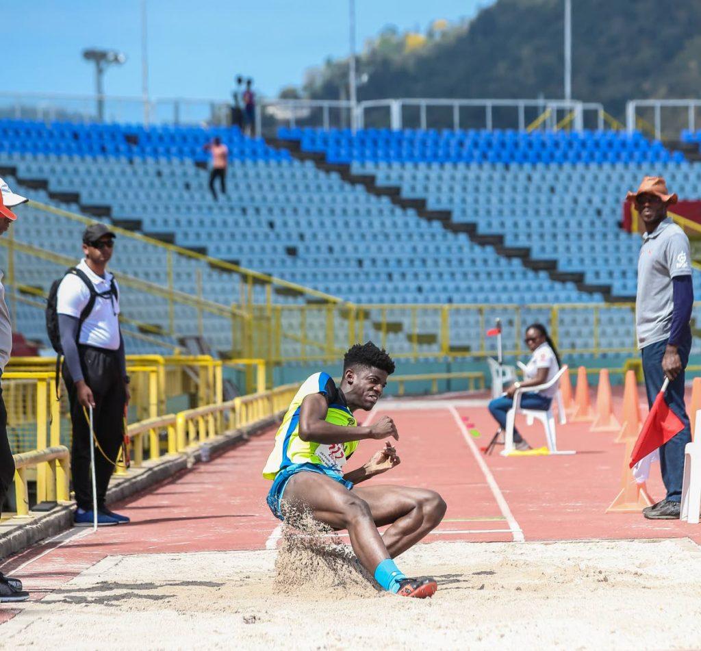 Neon Wolves' Jaydon Antoine lands on the sandpit during the boys Under-20 long jump yesterday.