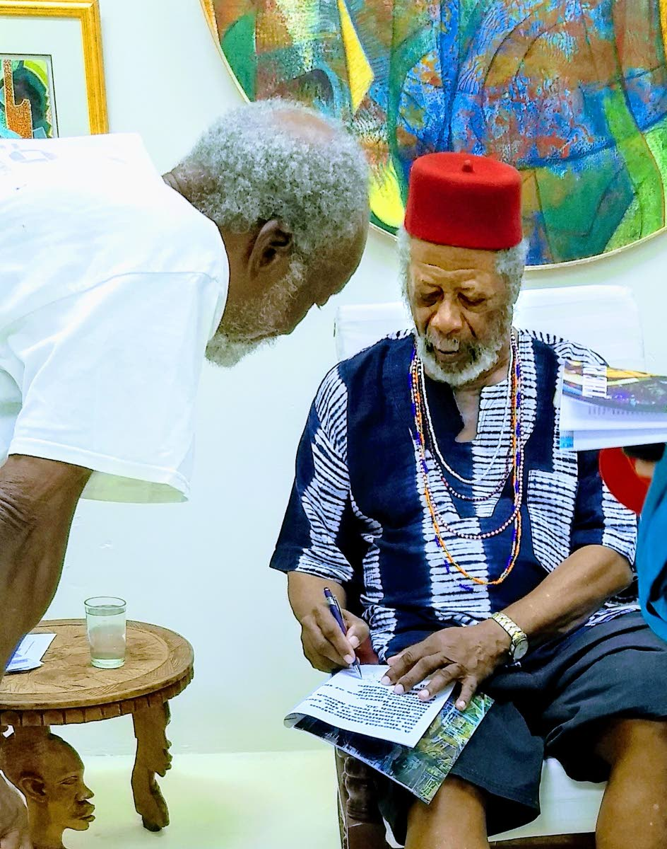 Artist LeRoy Clarke signs a commemorative copy of the T&T Review at the art show launch on March 19 at the Lloyd Best Institute of the Caribbean in Tunapuna.