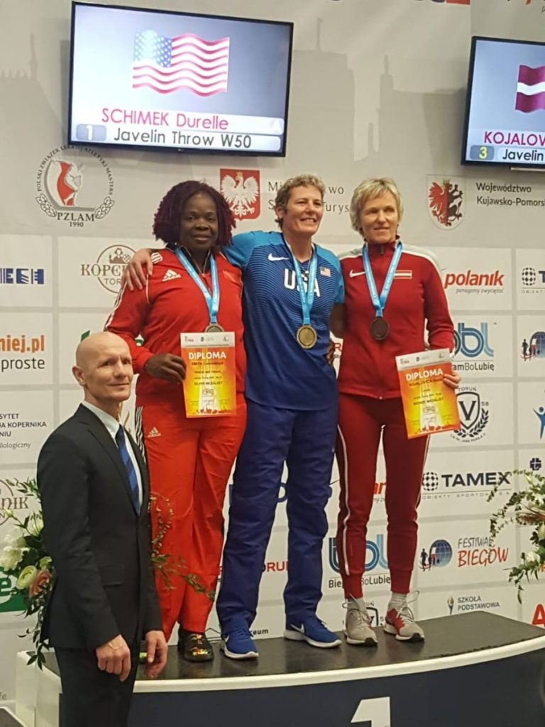 Gwendolyn Smith of TT, second from left, collects her women's 50-54 javelin silver medal at the 2019 World Masters Athletics Indoor Championships in Torun, Poland.
