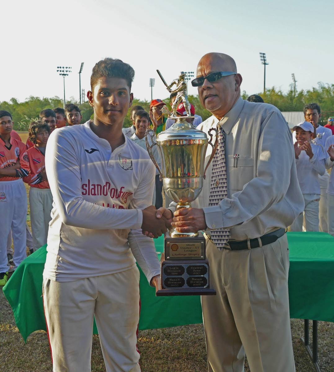 TT Under-15 player Justin Jagessar, left, collects a trophy from TT Cricket Board president Azim Bassarath, after leading the Central Zone to the U-15 Inter Zone title earlier this year. Jagessar scored 73 yesterday against Guyana in the Regional U-15 tournament. PHOTO COURTESY TTCB
