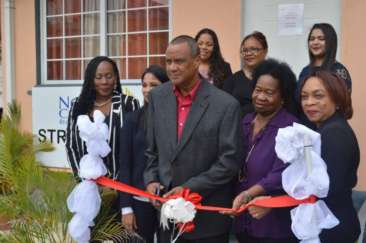 NCRHA's deputy chairman Elvin Edwards cuts the ribbon to officially open the NCRHA's Stress Relief Centre in Chaguanas. First row from left is Renee Pilgrim, NCRHA facilities manager - Chaguanas Cluster,  Ashvini Nath, Manager - Mental Health Services at Ministry of Health, NCRHA Director Yvonne Bullen-Smith and NCRHA's chief operations officer Stacy Thomas-Lewis. Members of the clinical team in the second row are clinical psychologists' Cavelle Delfosse, Patricia Lee-Wah Cooper and Samidha Maharaj.