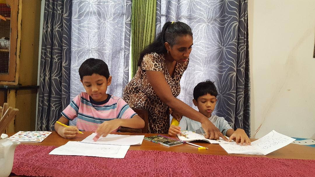Halena Kong Ting explains a point to her son Zachary, nine, while his brother, Rafael, seven, does some school work at home.