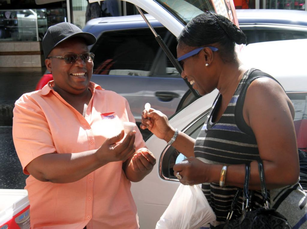 Tasters Premium Choice proprietor Karlene Dick, left, shares a sample of her homemade yogurt with a passer-by in Port of Spain.  PHOTO BY ANGELO MARCELLE