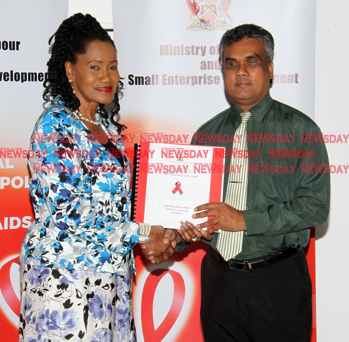 Labour and Small Enterprise Development Minister Jennifer Baptiste-Primus hands over copies of the National Workplace Policy on HIV and Aids, and an employee brochure document in braille, to Kenneth Surratt, executive officer of the Blind Welfare Association at the National Library, Port of Spain on Friday. PHOTO BY ANGELO MARCELLE