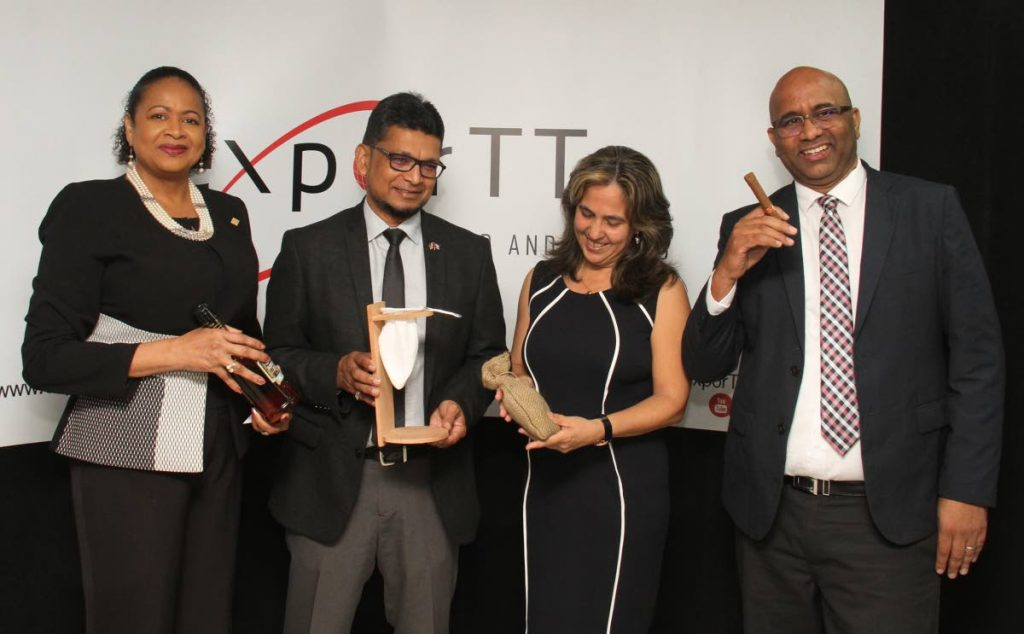 From left: Secretary General of the Association of Caribbean States, Ambassador Dr June Soomer, holds a bottle of Santiago De Cuba 11; while chairman of the board of directors, exporTT Ltd, Ashmeer Mohamed holds a coffee drainer; Ambassador of Cuba to TT Tania Diego Olite holds coffee beans; and  exporTT CEO Dietrich Guichard holds a cigar at the media launch of TT's participation in Expo Caribe 2019 at the exporTT Training Room, Charlotte Street, Port-of-Spain on Tuesday. PHOTO BY AYANNA KINSALE