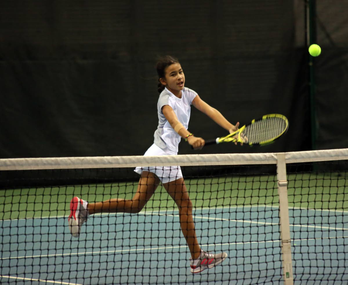 Jordane Dookie  returns to Jaeda-Lee Daniel-Joseph, in the girls Under-12 final, at the Catch National Junior Tennis Championship, at the National Racquet Centre, Tacarigua, yesterday.
