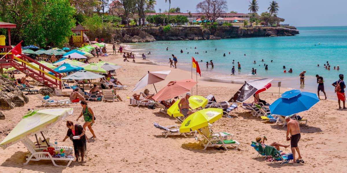 Tourists and locals enjoy a day at Store Bay earlier this year. Hotel occupancy rates in the island are said to be lower than normal. FILE PHOTO