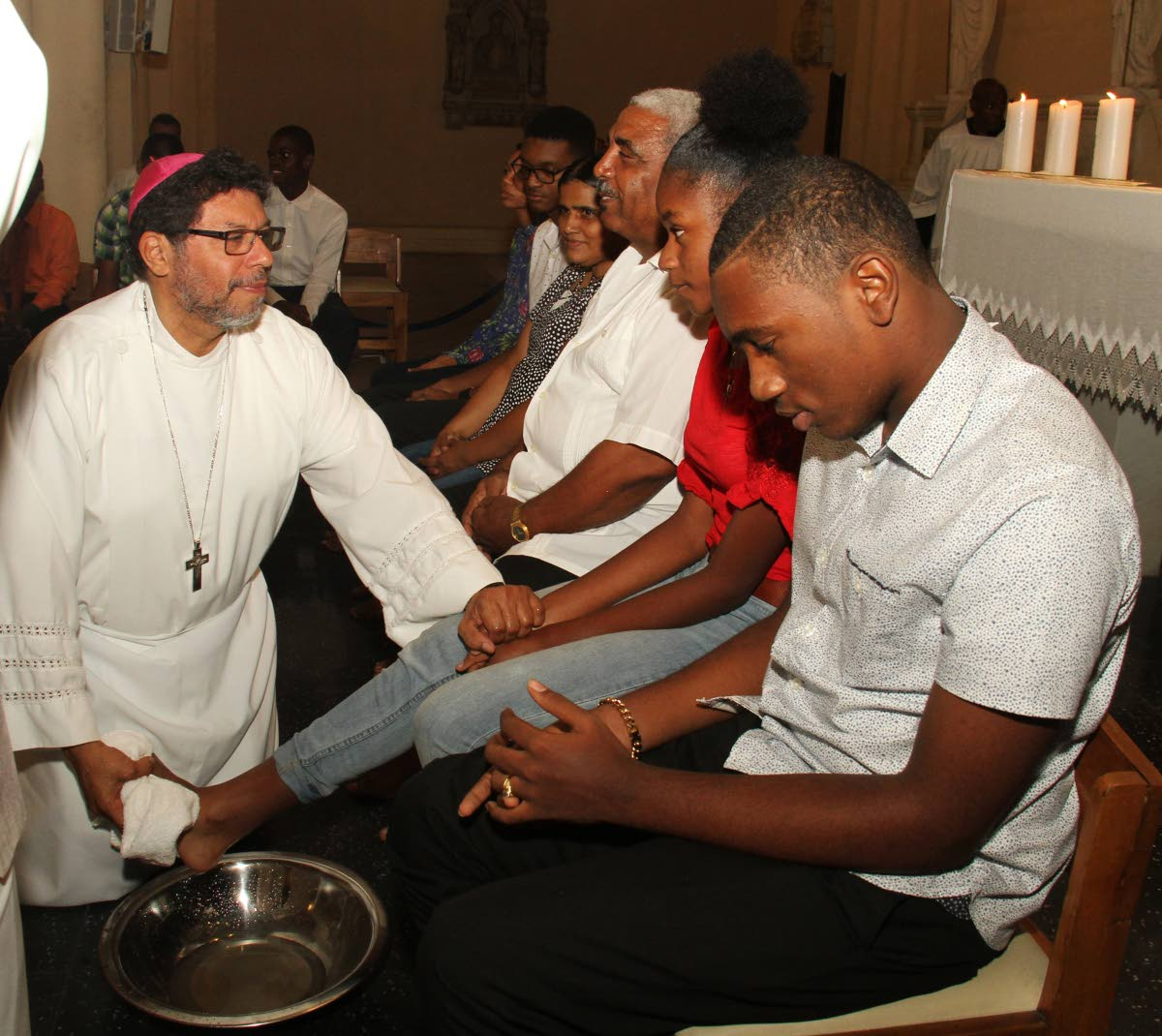 SERVANT: Archbishop of Port of Spain Jason Gordon washes the feet of Tyra Jack yesterday during Holy Thursday mass at the Cathedral of the Immaculate Conception in Port of Spain.