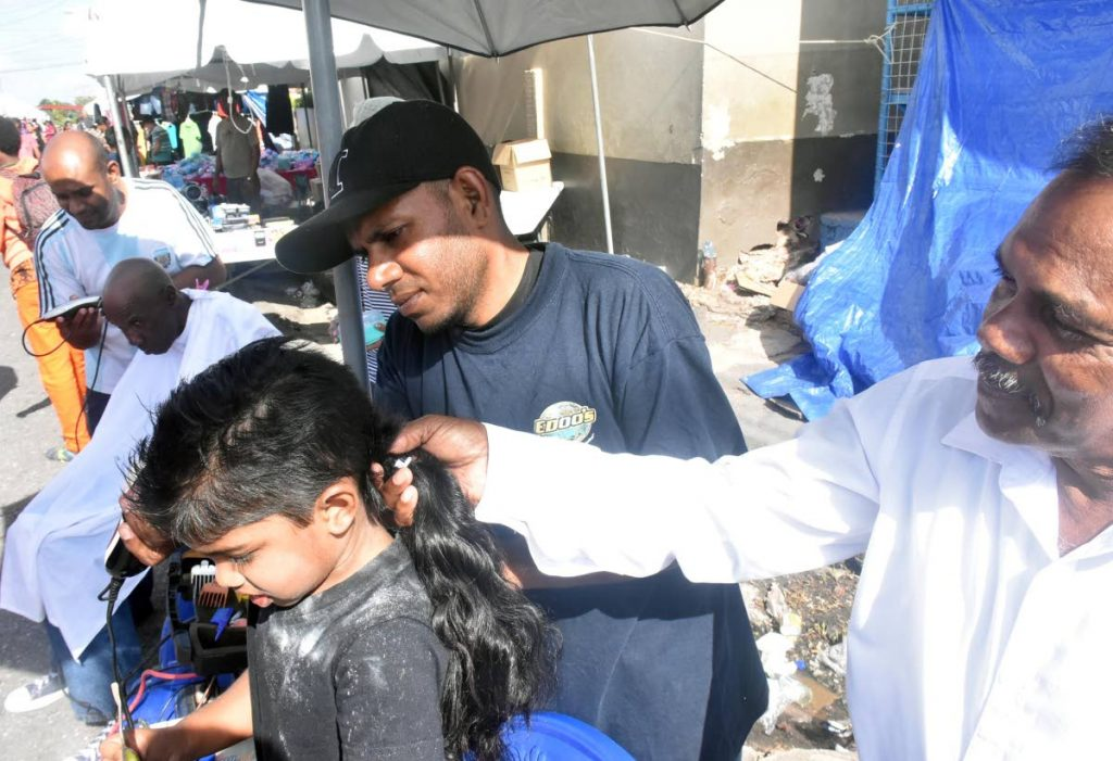 FIRST TIME: This boy gets his first haircut from barbers at the La Divina Pastora Church in Siparia yesterday.