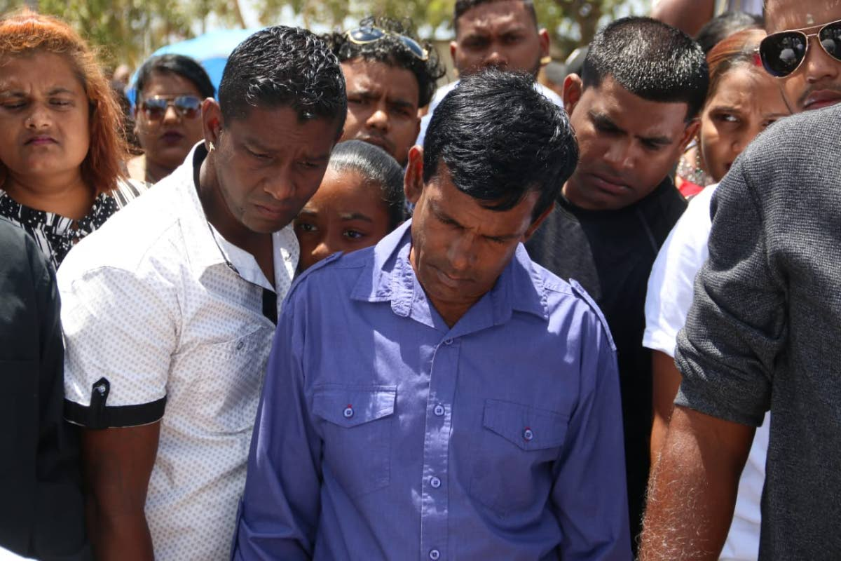 Survivor Kumar Lalla is seen looking on as the funeral of Ronald Narinesingh took place yesterday
