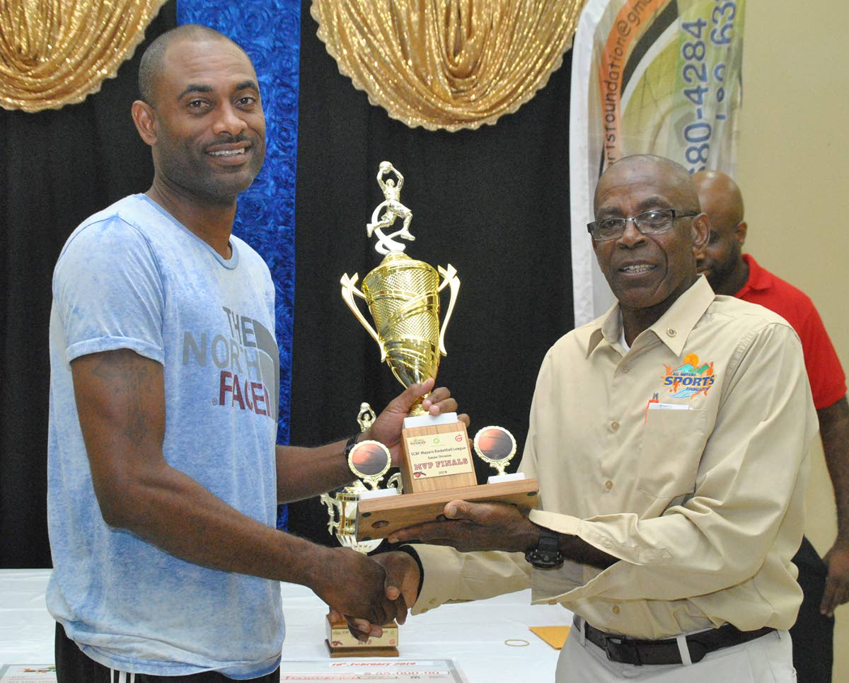 """Stephen """"Lighter"""" Lewis (left), of Matthew Pierre Basketball Academy, receives his MVP (Final) Senior Division trophy from AMSF's President Bartholomew Lynch."""