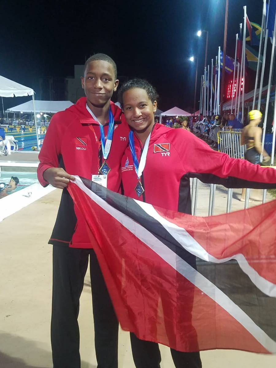 TT swimmers Nickolai Blackman, left, and Jada Chatoor with their Carifta gold medals in Barbados yesterday.