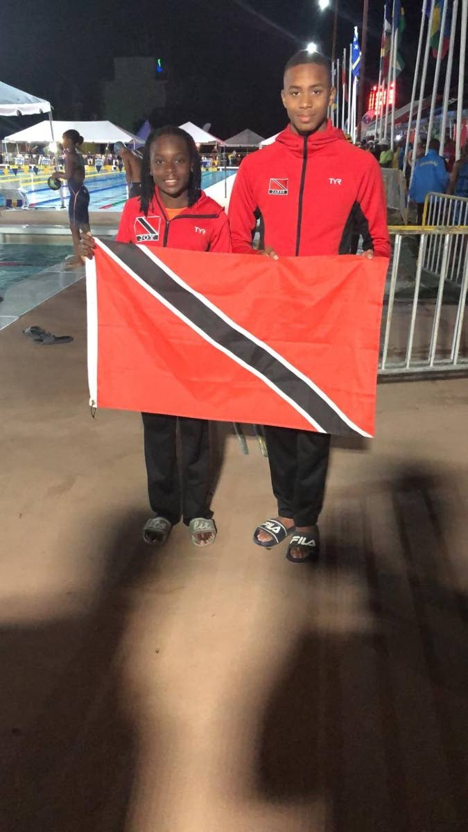 TT Carifta gold medallists Zarek WIlson, right, and Joy Blackett, with the national flag in Barbados. PHOTO BY SHERDON PIERRE
