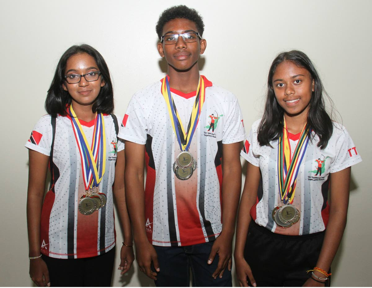 Members of the TT archery team Bryanna Ramlakhan,left, Darnell Garcia and Shanta  Roopchand, right, display their medals, on Tuesday night, at the Piarco Airport, after taking part in the Sourthern Caribbean Championships, held in Guadeloupe recently.