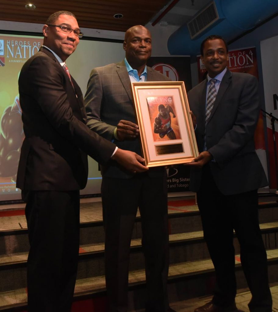 NGC's vice president of operations Ronald Adams, left,  and chairman of the Heroes Foundation Philip Julien, right, present Olympic 100m gold medallist Hasely Crawford with a framed copy of the first edition of the A Runner's Life - Lessons from an Olympian, at National Library, Port of Spain, on Thursday. PHOTO BY KERWIN PIERRE