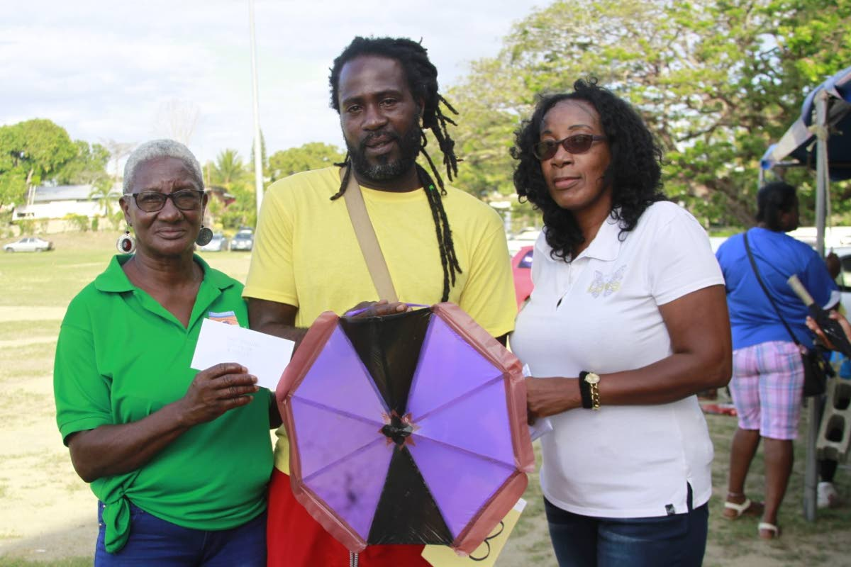 Pernell Smith, centre, who won three categories at the event, including best flying kite, receives his prize from Whim police Youth Club leader Sgt Mary Patrick, right, and club member Marilyn Spence.