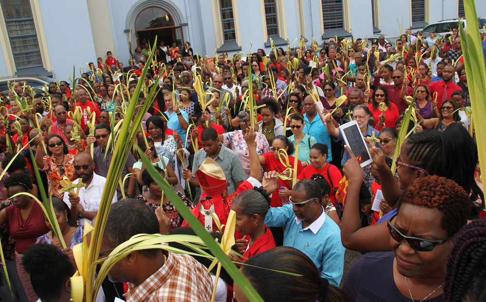 HOLY WEEK BEGINS: Archbishop Jason Gordon sprinkles holy water on the congregation at the Our Lady of Perpetual Help RC Church in San Fernando during Palm Sunday mass yesterday.   PHOTO BY VASHTI SINGH