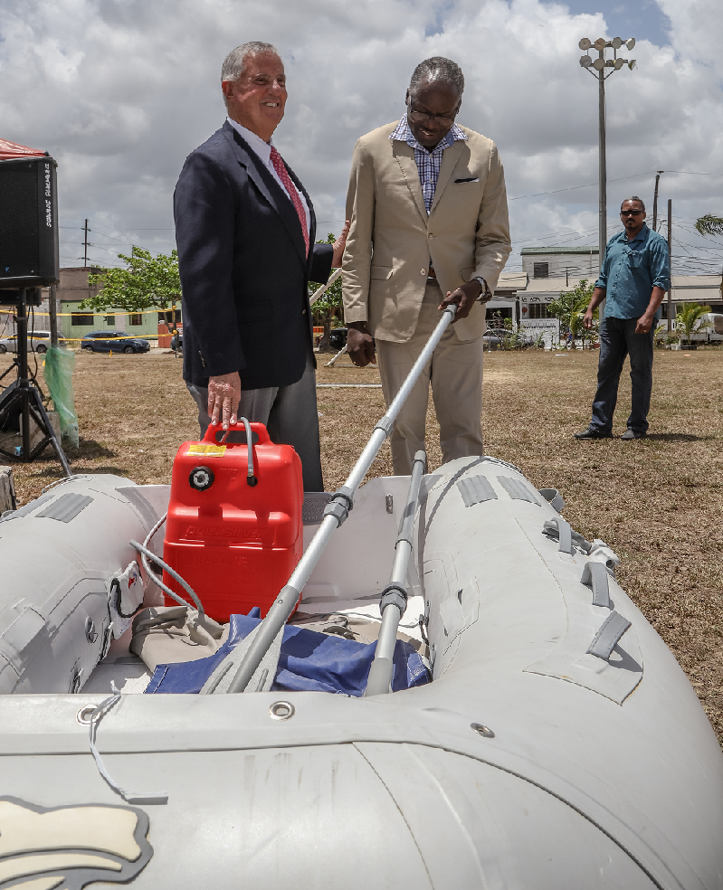 SAIL AWAY: US Ambassdor to TT Joseph Mondello and La Horquetta/Talparo MP Maxie Cuffie inspect one of the four inflatable boats donated to the Tunapuna/Piarco Regional Corporation yesterday.