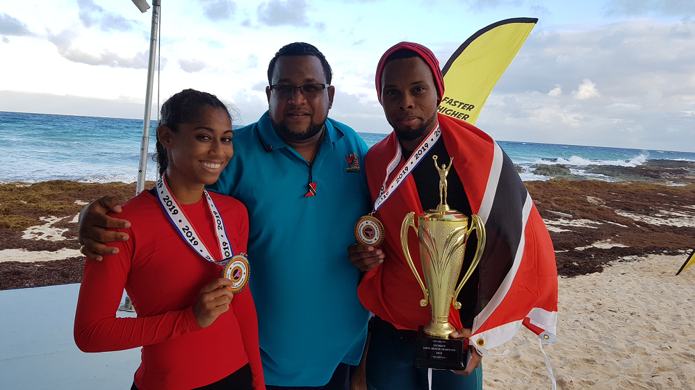 TT wrestlers Keron Bourne, right, and Minie Mayers, left, are congratulated by TT Wrestling Federation boss Jason Fraser, after winning medals at the Bridgetown Burning Championships recently.