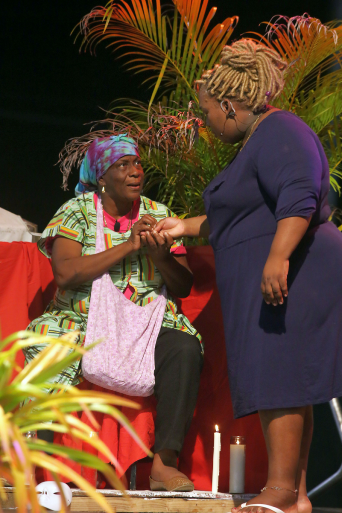 "Obeah woman Ticrissy (Brigetta Trim-James) gives counsel and a remedy to Beatrice (Giselle Yeates), on how to get her sister to agree to sell the family land in a scene from  Les Coteaux Close Connection Cultural Club's production of  ""Preserving ah we legacy, yuh honour,"" for the 2018 Tobago Heritage Festival at the Tablepiece recreation ground."